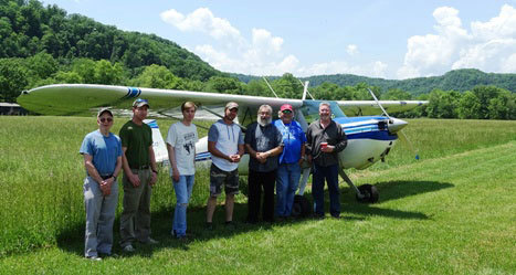 Class standing in front of small engine plane